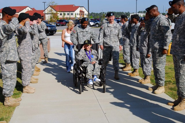 Sgt. Maj. Richard Harris, 1st Theater Sustainment Command G-4 sergeant major, escorts Ryan Beaulieu as he is greeted and saluted by Soldiers of the 1st TSC on his first stop during his tour of Fort Bragg. Ryan's wish to be a Soldier for a day was granted by The Make A Wish Foundation and Fort Bragg Sept. 16, 2010.
