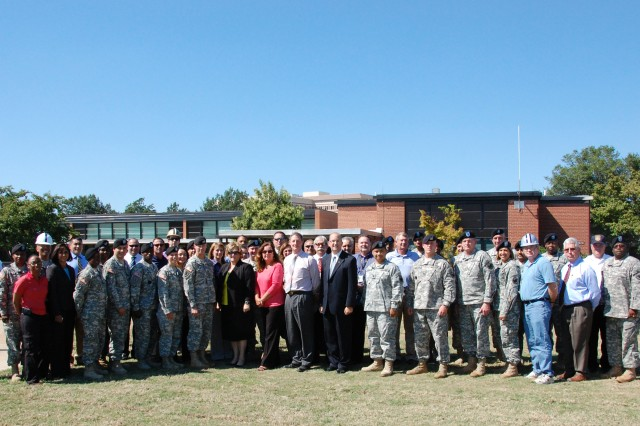 """With their new combined headquarters construction project visible in the distance, members of the U.S. Army Forces Command/U.S. Army Reserve Command Liaison and Torch Party elements pose for a group photograph in front of the Old Bowley School complex, Sept. 15, 2010, at Fort Bragg, N.C.  These Soldiers, their Army civilian counterparts and dedicated contractors are preparing the way for the arrival of  the advanced echelon from each command, set to begin arriving Oct. 1, 2010.  FORSCOM and USARC headquarters are moving to Fort Bragg from Fort McPherson, Ga., as directed by the 2005 Base Realignment and Closure Legislation."""""""
