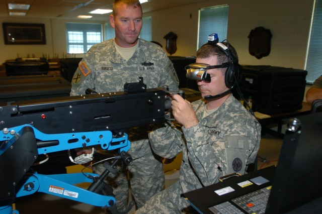 Staff Sgt. Anthony Burgess (center), a master gunner instructor with Charlie company, Warrior Training Center, Fort Benning, Ga., instructs Sgt. Peter Hyland, the unit administrator for 1st Detachment, Headquarters and Headquarters Company, 27th Brigade Special Troops Battalion, on the new .50-caliber individual gunnery trainer on Sept. 15, 2010, at the 27th Brigade armory.