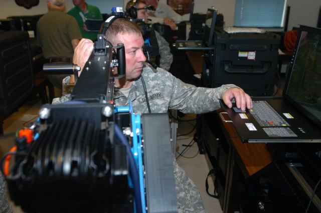 Sgt. First Class John White, an Engineer NCO with the 27th Infantry Brigade Combat Team, makes his way through the tutorial portion of the new .50-caliber individual gunnery trainer on Sept. 15, 2010, at the 27th Brigade Armory.