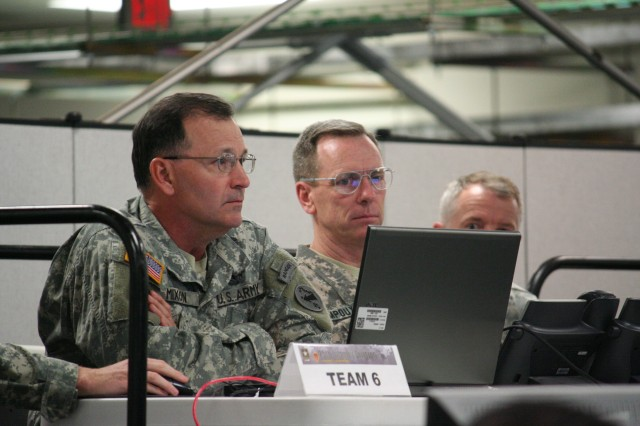 """Lt. Gen. Benjamin R. Mixon, commanding general, U.S. Army Pacific (left), is briefed on Division operations following a day of a simulated deployment scenarios during his visit to the First Lieutenant Nainoa Hoe Battle Command Training Center, at Schofield Barracks, Hawaii, Sept. 21. Maj. Gen. Bernard Champoux, commanding general, 25th Infantry Division, displayed the proficiency of his division operation center staff by showcasing their ability to react, adapt and communicate during the event to prepare the """"Tropic Lightning Division"""" for their upcoming deployment to Iraq."""