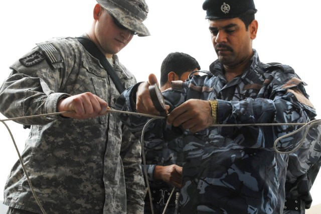 Spc. Simon Vogel, 731st Explosive Ordnance Disposal Company, 4th Advise and Assist Brigade, 3rd Infantry Division, shows Iraqi Police EOD members knot tying techniques during instruction at the Ramadi Training Center, Sept. 19, 2010.