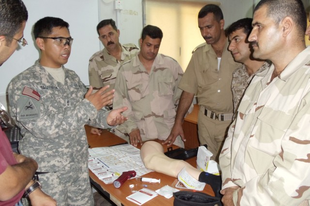 Sgt. 1st Class Melvin Bautista (second from left), clinical operations noncommissioned officer with the division surgeon's office with 1st Armored Division, United Division - Center, and Honolulu native, teaches Iraqi students in an first responder course how to use an Intravenous Infusion System Aug. 16 at a Ministry of Defense training facility in Baghdad. (Photo courtesy of 1st Armd. Div. surgeon's office)