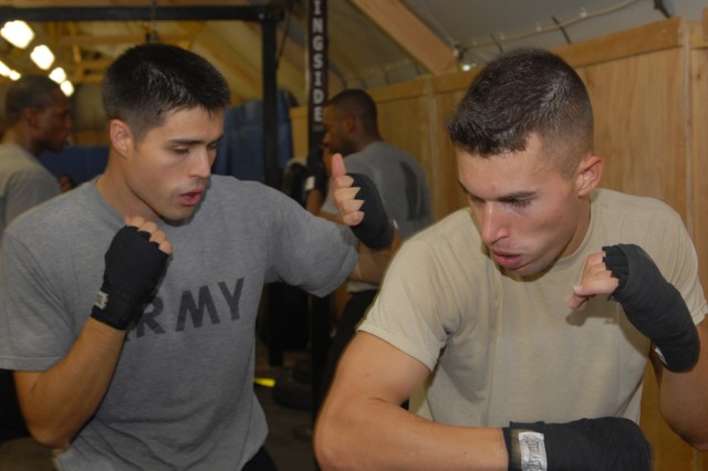 BAGHDAD - Pfc. Josiah Portukalian (left), a combat medic with B Company, Division Special Troops Battalion, 1st Armored Division, United States Division - Center, and an Orleans, Ind., native, practices a boxing technique Sept. 18 with Capt. William Conners, air battle captain for operations with Company A, DSTB, 1st Armd. Div., and a Wolcott, N.Y., native, at Camp Libery, Iraq. (U.S. Army photo by Cpl. Daniel Eddy, 196th MPAD, 1st Armd. Div., USD-C)