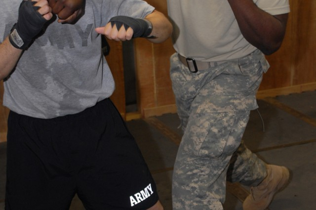 BAGHDAD - Staff Sgt. Jermaine Ellis (right), a logistical sergeant with Division Special Troops Battalion, 1st Armored Division, United States Division - Center, and a Youngstown, Ohio, native, demonstrates a proper boxing technique to Soldiers with Spc. Hilario Gonzales, a supply specialist with Company A, DSTB, and a Mission, Texas, native, Sept. 18 at Camp Liberty, Iraq. (U.S. Army photo by Cpl. Daniel Eddy, 196th MPAD, 1st Armd. Div., USD-C)