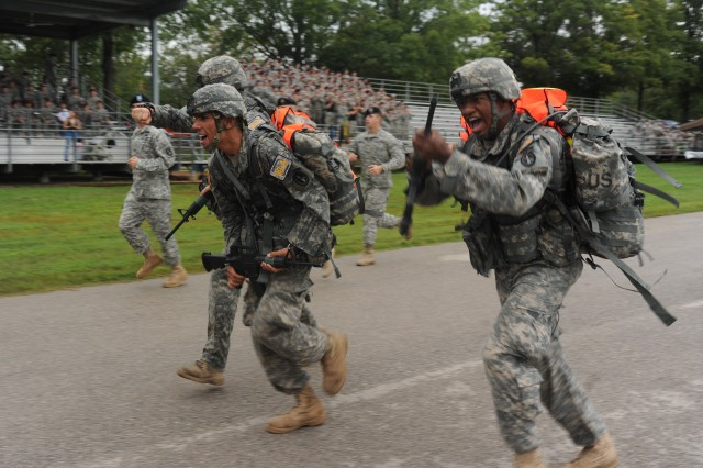 Cpl Christopher Vazquez, Spc. Greg Bartholomew and Spc. Deante Tarp of team 20 from the 289th Military Police Company out of Fort Myer, Va. cross the finish line as the first team to complete the final event of the MP Warfighter competition: the 15-mile endurance march, at Fort Leonard Wood, Mo., Sept. 16.