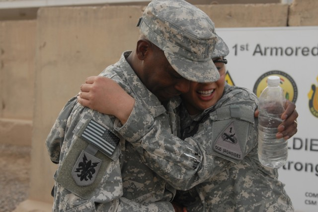 BAGHDAD - 1st Lt. Aiana Janica Garin (right), a communication officer with B Company, Division Special Troops Battalion, 1st Armored Division, United States Division - Center, and a Bremerton, Wash., native, is congratulated by Chief Warrant Officer 5 Randy Johnson, the division maintenance officer for the 1st Armd. Div., and a Galveston, Texas, native, after her promotion from second lieutenant Sept. 19 at Camp Liberty, Iraq. (U.S. Army photo by Cpl. Daniel Eddy, 196th MPAD, 1st Armd. Div., USD-C)
