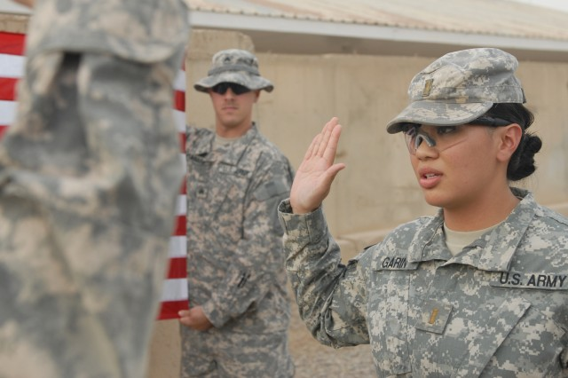BAGHDAD - 2nd Lt. Aiana Janica Garin (right), a communication officer with Company B, Division Special Troops Battalion, 1st Armored Division, United State Division - Center, and a Bremerton, Wash., native, reaffirms her commissions oath Sept. 19 as she is promoted to first lieutenant by Lt. Col. Lane Turner, commander of DSTB, 1st Armd. Div., and an Atlanta native, during a ceremony at Camp Liberty, Iraq. (U.S. Army photo by Cpl. Daniel Eddy, 196th MPAD, 1st Armd. Div., USD-C)