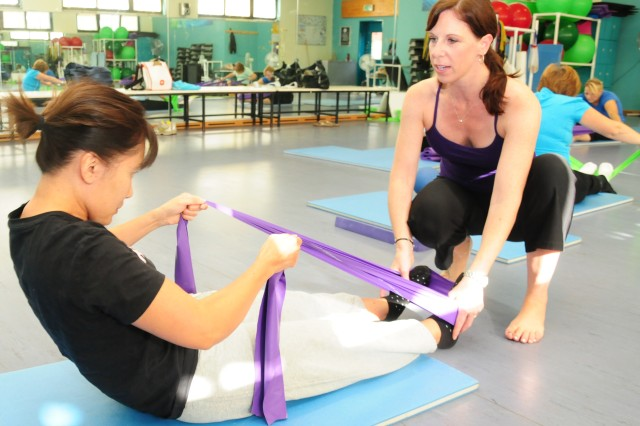 Stasia Bryant, Pilates instructor for Heidelberg Sports and Fitness assists one of her students, Yuko Daniels during a Pilates class in Heidelberg, Germany. The Family, Morale, Welfare and Recreation class is just one of many offered to help keep Soldiers, families and civilians fit to fight.