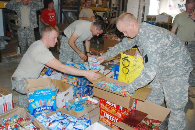 Soldiers of the 717th Military Intelligence Battalion set up snacks for inclusion in boxes destined for troops deployed overseas. The Soldiers volunteered through the Better Opportunities for Single Soldiers program to work with the Soldiers' Angels organization for the afternoon of Sept. 10.