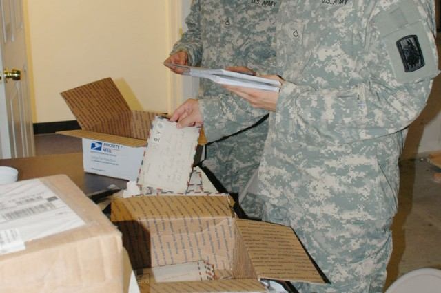 Two Soldiers of the 717th Military Intelligence Battalion sort mail for inclusion in packages going to troops overseas.