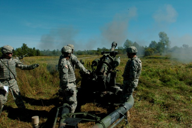 FORT DRUM, NY--A 105mm high explosive round leaves the tube of an M119A2 and heads toward the target downrange during a live fire exercise Sept. 17 at the Fort Drum artillery range.  The unit received new howitzers and this weekend drill was the battalion's first live fire exercise with its new 105 millimeter guns. The new modern artillery pieces replace the M-102 howitzer's the battalion had been borrowing to train with.