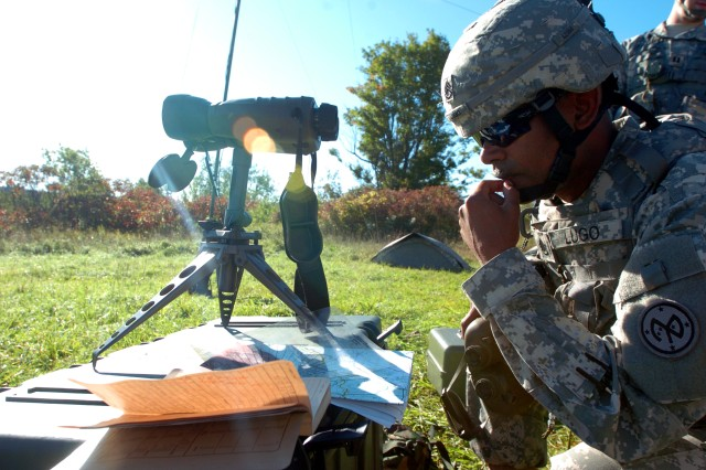 FORT DRUM, NY--Staff Sgt. Onix Lugo, platoon sergeant for the target acquisition section, Headquarters Battery, 1-258th Field Artillery , New York Army National Guard, reviews a map of the impact zone and calculates corrections for the battery fire direction center during live fire training at the Fort Drum artillery range September 16-19.