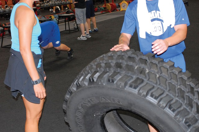 Ms. Joanne Cain, fitness program manager at Audie Murphy Athletic Center, leads SGT Eddie Smigelski through a tire-flipping drill Wednesday. She's the strength, conditioning and agility coach for the 3rd Heavy Brigade Combat Team football squad, which is preparing for an Oct. 28 game against Columbus State University's club team at Doughboy Stadium.