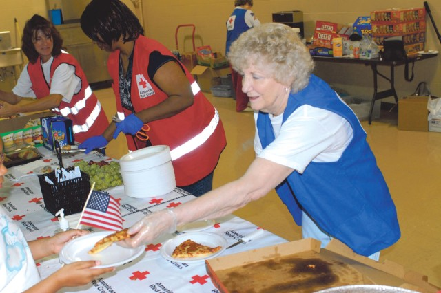 From right, Ms. Iris Poole, Ms. Linda Rias and Ms. Kathy Fegurgur of the Red Cross serve up free pizza Friday to families waiting at Freedom Hall.