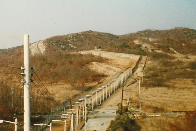 """View from the tower at Guard Post 128 looking northeast along the southern boundary of the DMZ in 1989.  GP 128 was the only entrance into the American sector of the DMZ during that time.  In the middle ground of the photo can be seen the 2nd Infantry Division (""""Indianhead"""") insignia and the Expert Infantry Badge."""