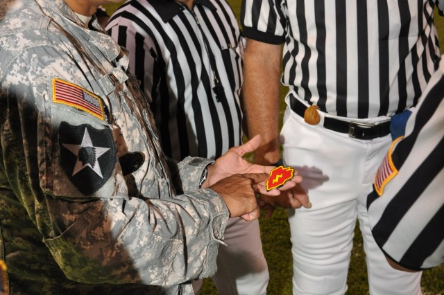 25th Infantry Division Command Sergeant Major Frank Leota tells the history of the Tropic Lightning embodied in its challenge coin to the referees prior to the Leilelua versus Radford Hight School Sept. 24. The challenge coin was used in the coin toss. (U.S. Army photo by Lt. Col. Sean Wilson, 25th Infantry Division Public Affairs Office)