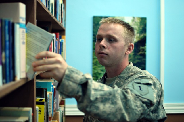 Pfc. Garret Shoemake, a Soldier serving in Iraq with the Enhanced Combat Aviation Brigade, 1st Infantry Division, browses the Taji Warrior Resiliency Campus's library, Sept. 24.
