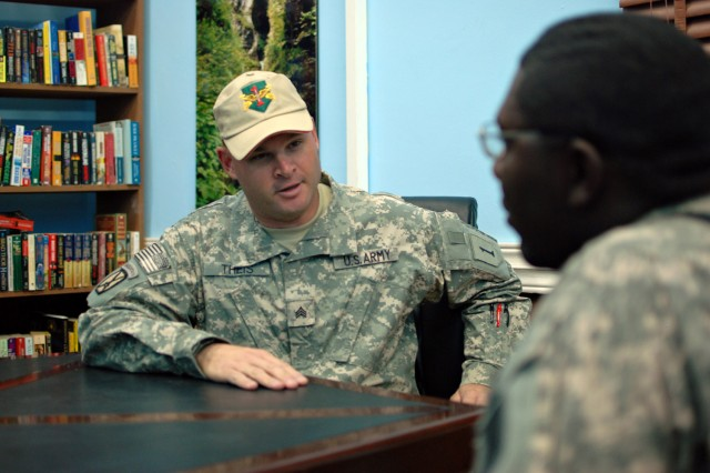 Sgt. David Theis, a noncommissioned officer working at the Taji Warrior Resiliency Campus on Camp Taji, Iraq talks with a Soldier in the campus's library, Sept. 24. The campus is staffed 24-hours a day to provide guidance and access to recreation.