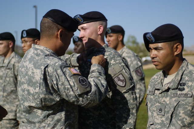 "FORT IRWIN, Calif.-Col. Antonio Aguto Jr., the 11th Armored Cavalry Regiment commander, pins the Expert Infantryman Badge on Pvt. Brandyn Doerle, F Troop, 2nd Squadron, 11th ACR, during an EIB pinning ceremony at the National Training Center on Fort Irwin, Calif., Sept. 24. Doerle, 22, of St. Louis, Mo., was the only ""true blue"" EIB candidate which meant he scored perfect on all testing lanes. (Photo by Sgt. Giancarlo Casem, 11th ACR Public Affairs)"