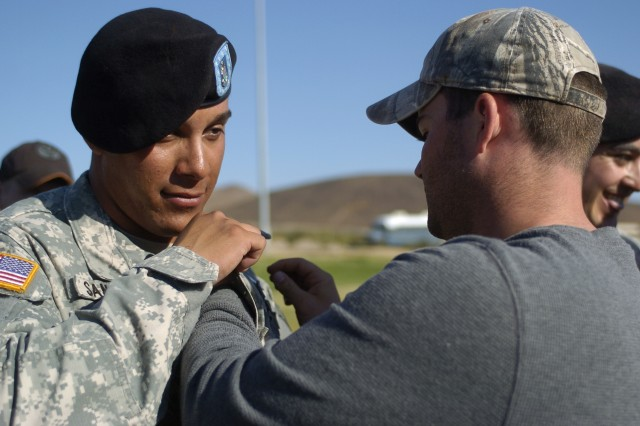 FORT IRWIN, Calif.-Grapevine, Texas, native Sgt. Jerry King, F Troop, 2nd Squadron, 11th Armored Cavalry Regiment, pins the Expert Infantryman Badge on Spc. David Sanchez during an EIB pinning ceremony at the National Training Center on Fort Irwin, Calif., Sept. 24. Sanchez, also from F Troop and a native of Vista, Calif., was one of 33 Soldiers who earned their EIB during the ceremony. The five-day testing event started with more than 200 Soldiers vying for the coveted badge. (Photo by Sgt. Giancarlo Casem, 11th ACR Public Affairs)