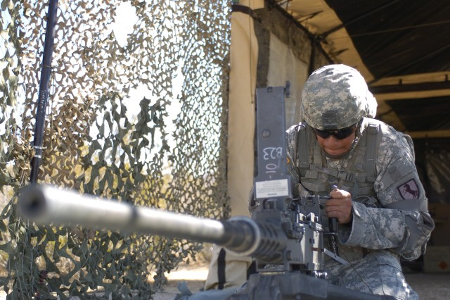 FORT IRWIN, Calif.-Vista, Calif., native Spc. David Sanchez, F Troop, 2nd Squadron, 11th Armored Cavalry Regiment, attaches the trigger mechanism to an M2 .50 caliber machine gun during the evaluation phase of the Expert Infantryman Badge test at the National Training Center on Fort Irwin, Calif., Sept. 23. (Photo by Sgt. Giancarlo Casem, 11th ACR Public Affairs)