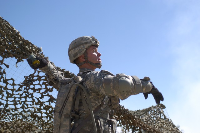 FORT IRWIN, Calif.-Sgt. Jedidiah Schuyten, 11th Armored Cavalry Regiment, throws a smoke grenade during the evaluation phase of the Expert Infantryman Badge test at the National Training Center on Fort Irwin, Calif., Sept. 23. (Photo by Sgt. Giancarlo Casem, 11th ACR Public Affairs)