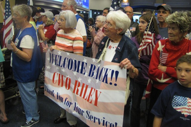 Hundreds of family members and community well-wishers with signs and flags pack the corridor at the Huntsville International Airport as they wait for WWII veterans to return from the last Honor Flight.