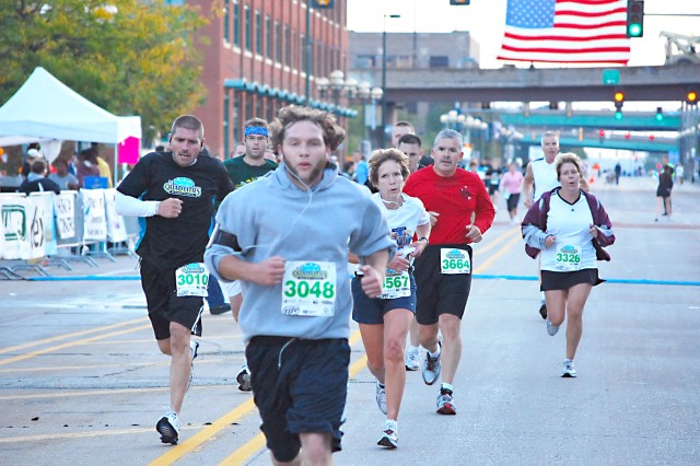 Half-marathon participants vie against each other as they earnestly run toward the finish line.