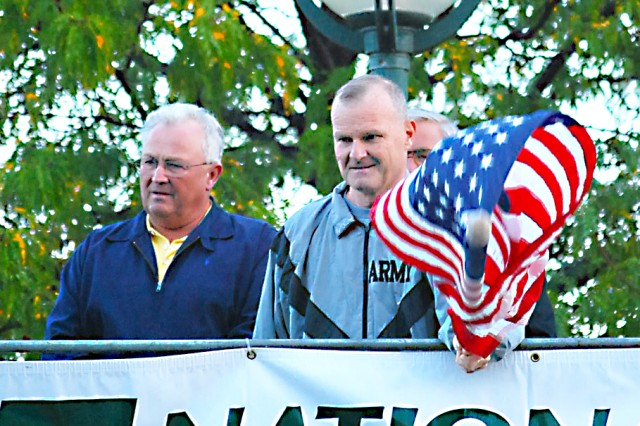 Maj. Gen. Yves J. Fontaine, commanding general of the Army Sustainment Command, signals the start of the 13th annual Quad Cities Marathon held Sept. 26 in Moline, Ill., flanked by Mayor Don Welvaert.