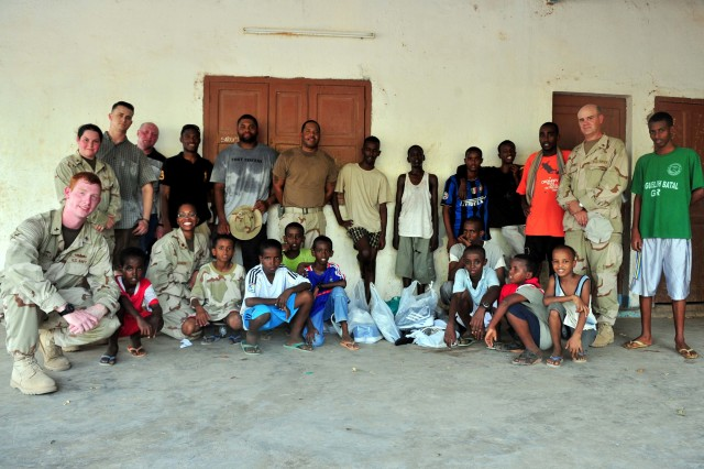 Children of the National Center For the Protection of Juvenile Boys pose for a photo with volunteers of Combined Joint Task Force-Horn of Africa September 16, 2010. After a game of soccer, the volunteers presented the boys with new shoes collected from personnel around Camp Lemonnier.