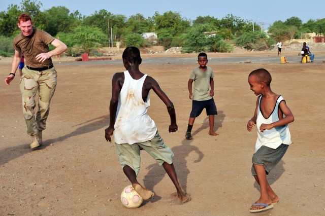 U.S. Navy Cryptological Technician Collection 2nd Class Jeremy Gottschalk, Combined Joint Task Force-Horn of Africa, plays soccer with children of the National Center For the Protection of Juvenile Boys September 16, 2010. Gottschalk and other volunteers presented the boys new shoes, collected from personnel around Camp Lemonnier, after the game.