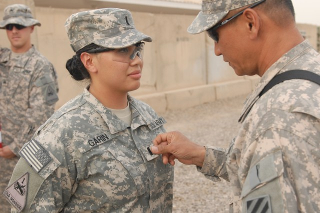 2nd Lt. Aiana Janica Garin, left, a communications officer with Company B, Division Special Troops Battalion, 1st Armored Division, U.S. Division - Center, is promoted to first lieutenant by her father, Army Warrant Officer Romeo Garin, during a Sept. 19 ceremony at Camp Liberty, Iraq.