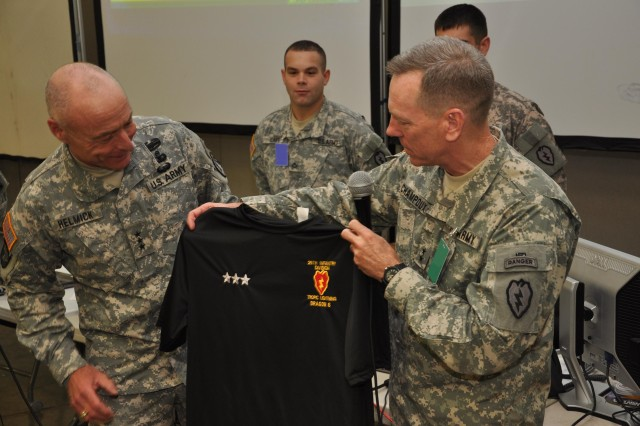 Maj. Gen. Bernard Champoux (right), commanding general, 25th Infantry Division, presents Lt. Gen. Frank Helmick (left), commanding general, 18th Airborne Corps, with a personalized 25th Infantry Division physical training t-shirt as a token of  appreciation durring their Mission Readiness Exercise at Schofield Barracks, Hawaii, Sept. 27. Helmick and Champoux will work together again once again when both commands deploy in support of Operation New Dawn in Iraq later this year. (U.S. Army photo by Spc. Mahlet Tesfaye, 25th Infantry Division Public Affairs Office)