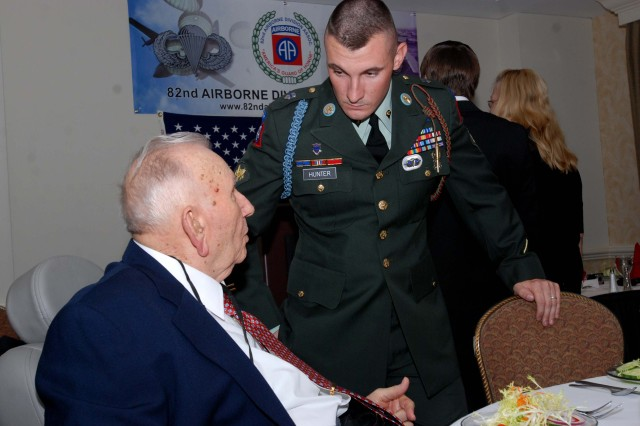 Spc. Marcus Hunter, C Co., 1st Battalion, 325th Airborne Infantry Regiment, 2nd Brigade Combat Team, speaks with Harold Owens, a World War II 325th Glider Infantry Regiment veteran at the 325th GIR reunion in Charlotte, NC on Sep. 25. As the last reunion for the veterans, Paratroopers with 1/325 came to the event to honor the men, listen to their stories, and presented them with certificates of appreciation and 2BCT coins. (U.S. Army photo by Spc. Kissta M. Feldner, 2BCT PAO)