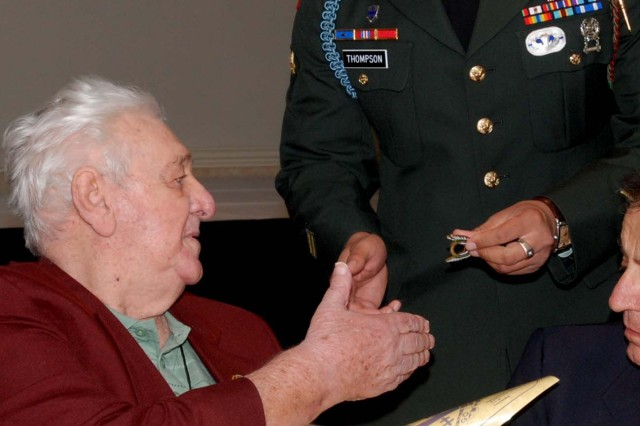 Spc. Carlos Thompson, C Co., 1st Battalion, 325th Airborne Infantry Regiment, 2nd Brigade Combat Team, presents a certificate of appreciation and a 2BCT coin to Jack Cimino, a WWII veteran of the former 325th Glider Infantry Regiment at the final 325th GIR reunion in Charlotte, Sep. 25. Five 2BCT Paratroopers attended the event to pay respect to the veterans, whose unit paved the way for 2BCT. (U.S. Army photo by Spc. Kissta M. Feldner, 2BCT PAO)