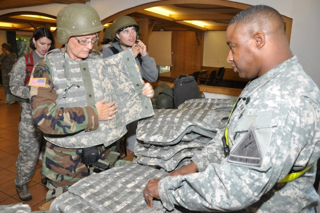 Sgt. 1st Class Nazerine Howard helps spouses adjust their TA-50 gear during 1st Armored Division's Combat Spouses Day Sept. 22.