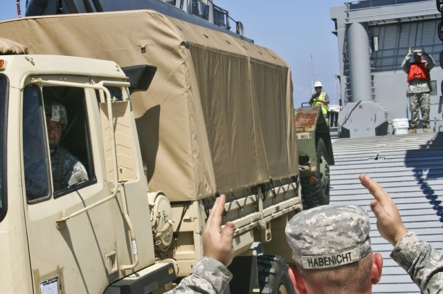 """Pfc. Jordan Habenicht, with the Tacoma, Washington-based Army Reserve's 709th Transportation Company, guides a Light Medium Tactical Vehicle (LMTV) onto the deck of the Landing Craft Utility (LCU) 2007 """"Calaboza,"""" during Pacific Reach 2010, Sept. 1, at Ito City, Japan. Pacific Reach 2010 is a validation of the issue and turn-in process of two LCU 2000-series boats from Army Prepositioned Stocks-4 (APS-4). The exercise, which was conducted from Aug. 31 through Sept. 2, took the watercraft from the stock and ran them through a simulated humanitarian aid and relief mission to Ito City, some 60 nautical miles south of Yokohama, Japan. The major maintenance and storage facilities for APS-4 are at the 403rd Army Field Support Battalion - Northeast Asia at Camp Carroll, Korea, and at Sagami Army Depot, Japan. (Photo by Sgt. 1st Class Sean Riley, ASC Public Affairs)"""