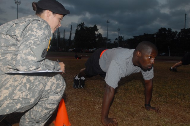 SCHOFIELD BARRACKS, Hawaii - Staff Sgt. Trisha Melgar, 25th Inf. Div. Headquarters Support Company, grades Sgt. Antonio Foy, a court reporter with the U.S. Army, Japan, as he performs the push-up portion of the Army Physical Fitness Test at the U.S. Army, Pacific Paralegal Warrior Challenge. Eight top paralegal Soldiers from units throughout the Pacific began the week of competition with an APFT at Schofield Barracks' Stoneman Field.