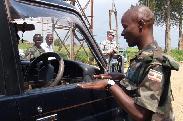 Capt. Jedmund Greene (in background), 21st Theater Support Command, 16th Sustainment Brigade, based in Kaiserslautern, Germany, takes part in mentoring Ugandan military logisticians in vehicle measurement for deployment during air load planning certification in Entebbe, Uganda.""