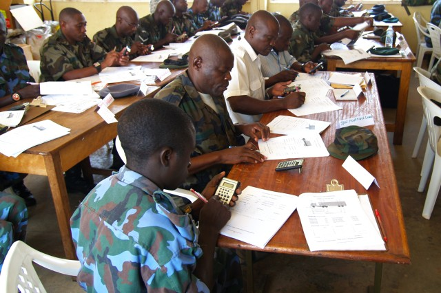 Uganda People's Defense Force (UPDF) logisticians crunch the numbers during a classroom segment of Uganda ADAPT 2010, a mentoring program conducted in Entebbe, Uganda, that resulted in certifying 25 soldiers as C-130 aircraft load planners.