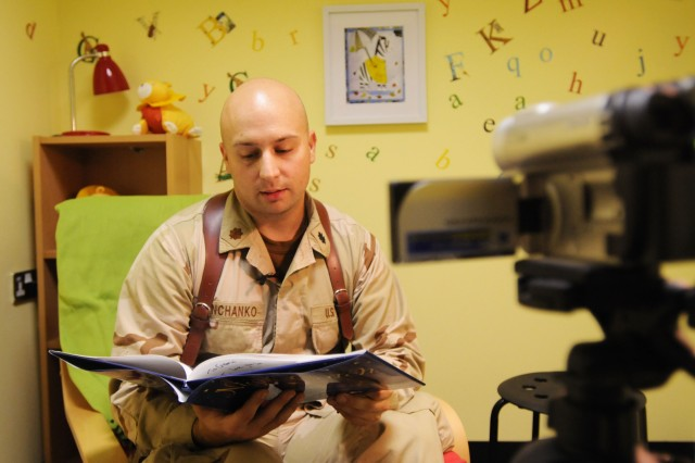 Lt. Cmdr. William Danchanko, a nurse practitioner at Role 3, the hospital on Kandahar Air Field, Afghanistan, videotapes a recording of himself reading a book for his 2-year-old son Sept. 27. The USO at KAF has three reading rooms and allows servicemembers to read, record, and send one book home per day. (U.S. Army photo by Spc. Jennifer Spradlin, 16th Mobile Public Affairs Detachment)