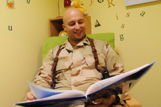 Lt. Cmdr. William Danchanko, a nurse practitioner at Role 3, the hospital on Kandahar Air Field, Afghanistan, pre-reads the book he has selected for his son prior to recording it Sept. 27. Since USO and United Through Reading partnered in 2006, more than 100,000 books have been sent home for children to enjoy while their parent is deployed. (U.S. Army photo by Spc. Jennifer Spradlin, 16th Mobile Public Affairs Detachment)