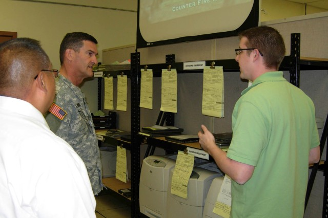 Tim Goodrich (right), electronics digital computer mechanic, explains the process of receiving and returning electronic repairs at Tobyhanna's Forward Repair Activity (FRA) to Maj. Gen. Randolph P. Strong, commanding general of the Army Communications-Electronics Command, during his Sept. 23 visit to Joint Base Lewis-McChord, Wash.  Tobyhanna's FRA West Branch directs nearly 100 employees based at several military installations on the west coast and in Hawaii, Alaska, Korea and Japan.