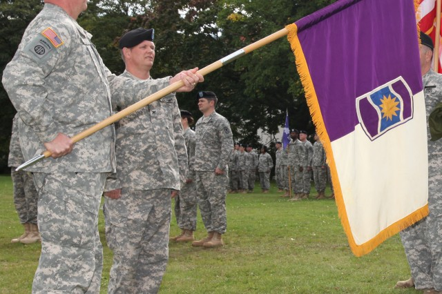 Brig. Gen. Jimmie Jaye Wells, the 7th Civil Support Command's commanding general, unveils the new 361st Civil Affairs Brigade colors during an activation ceremony for the 361st CA. Bde. and the 457th Civil Affairs Battalion on Daenner Kaserne's parade field Sept 17.