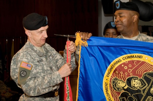 Maj. Gen. Nick Justice, commanding general of the Army Research, Development and Engineering Command (RDECOM), puts the Army Superior Unit streamer on the RDECOM flag during an awards ceremony Sept. 22 at Picatinny Arsenal, N.J. The ceremony recognized the entire ARDEC workforce for its significant achievements for the warfighters in 2007 during GWOT.