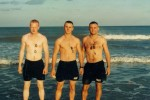 Three Soldiers staning in the ocean with their swimssuits and dog tags on