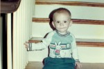 Staff Sergeant Robert Miller as a baby sitting on the stairs