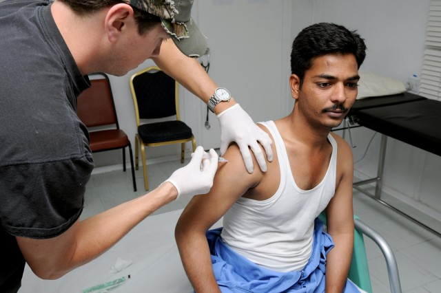 Cory Brown, a native of San Diego, administers an anti-inflammatory medication to Murali Veau, a native of Hyderabad, India and a housekeeper employee for one of the contractors in Basra Sept. 23. Brown is a civilian paramedic providing medical and health care services to third-country nationals who are employed on post.