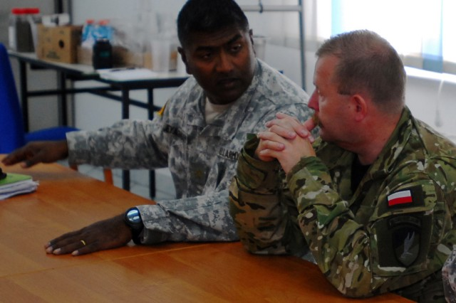 Maj. Jeyanthan Jeyasingam, left, contracting officer assigned to 643rd Contingency Contracting Team out of Grafenwoehr, Germany, and Polish Lt. Col. Miroslaw Krupa discusses contractual issues and concerns during their daily meeting held at the 21st Tactical Airbase in Swidwin, Poland as part of the Jackal Stone 10 exercise.  Jackal Stone is an annual international special operations forces (SOF) exercise held in Europe. Its objective is to enhance capabilities and interoperability amongst the participating special operations forces as well as build mutual respect while sharing doctrinal concepts. The exercise, which is coordinated by U.S. Special Operations Command Europe, includes Poland, Lithuania, Latvia, Croatia, Romania, and Ukraine. (U.S. Army photo by Staff Sgt. Shelia L. Sledge )